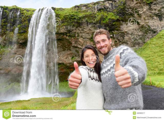 iceland-couple-thumbs-up-wearing-icelandic-sweater-seljalandsfoss-waterfall-ring-road-beautiful-nature-landscape-48390517